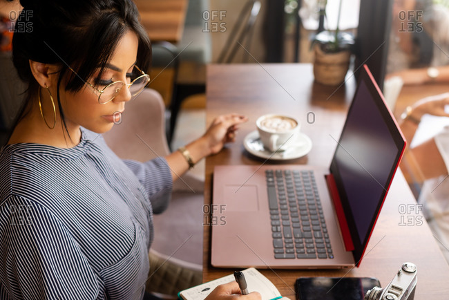 girl having a coffee while working in a cozy environment