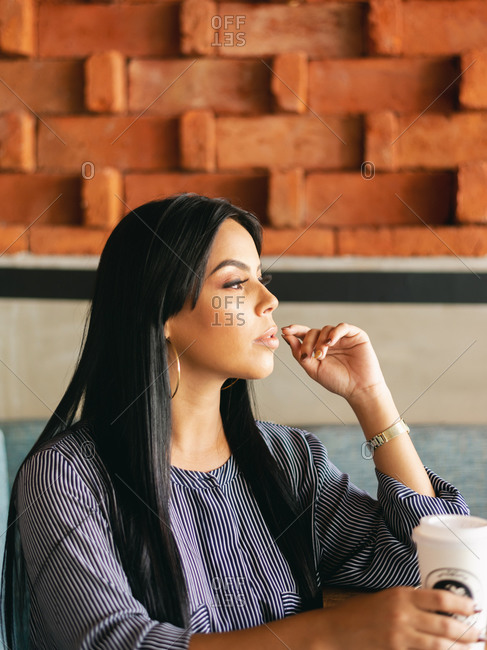 woman thinking and looking somewhere, while having a coffee