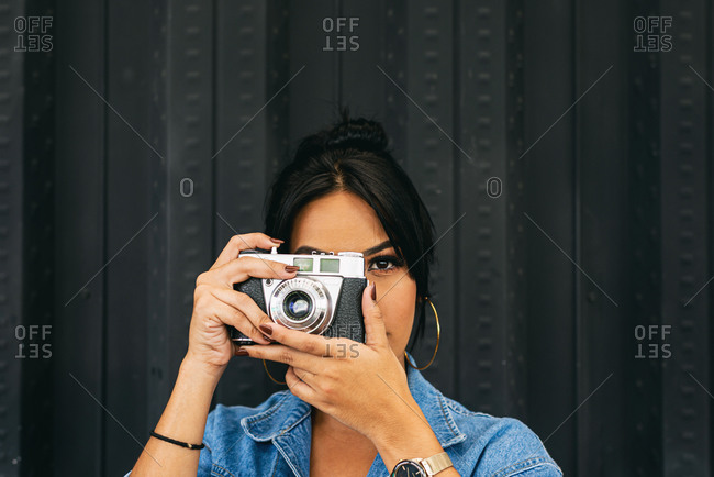 taking a picture with an antique camera, woman in fashionable clothes