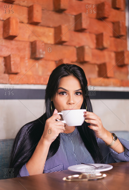 portrait of a woman while enjoying a coffee, in a coffee shop in the c