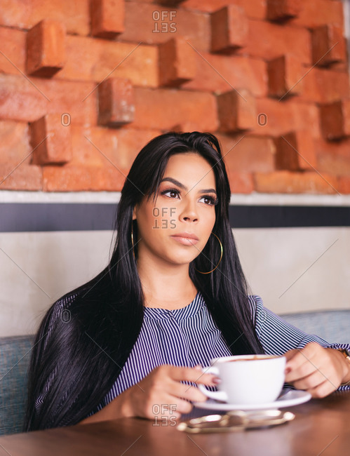 portrait of woman over coffee, brick background