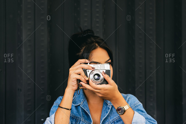 woman with an industrial background taking a photograph, camera