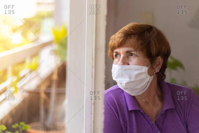 Elderly watches through the window of her house, while being confined by the coronavirus quarantine.....