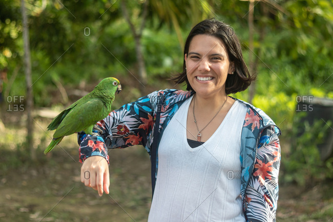 Woman poses with a smile as she carries her arm to a macaw in a camp