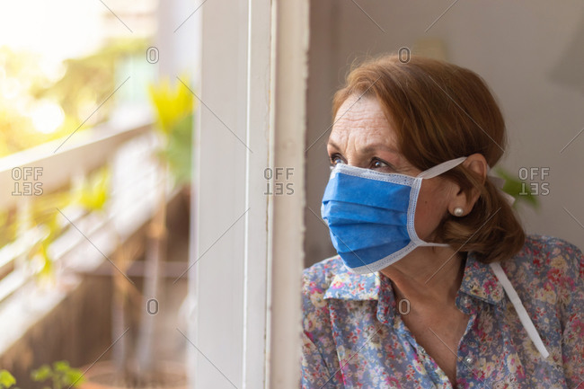 Elderly watches through the window of her house