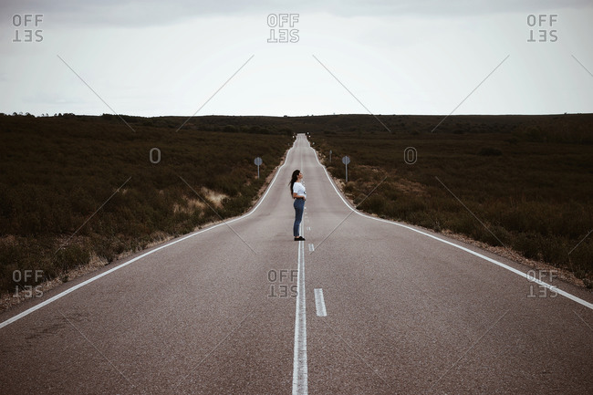 Young Spanish girl, in the middle of a lonely road, during summer.