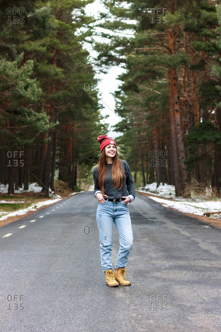 Happy young girl walking in the middle of lonely road in snowy forest.