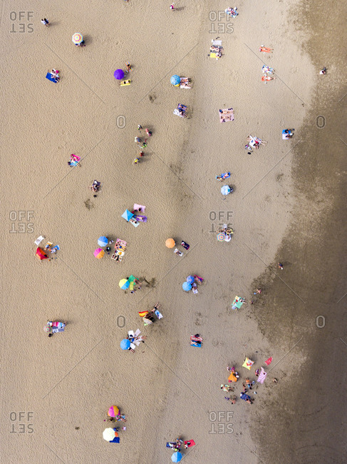 Beach filled with people and colorful umbrellas from a bird's eye view