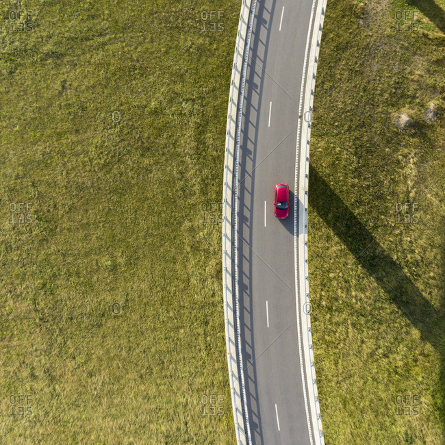 Aerial view of a red car driving on the roadway