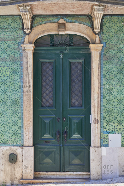 Dark green door surrounded by Moorish tile in the Lapa neighborhood, Lisbon, Portugal