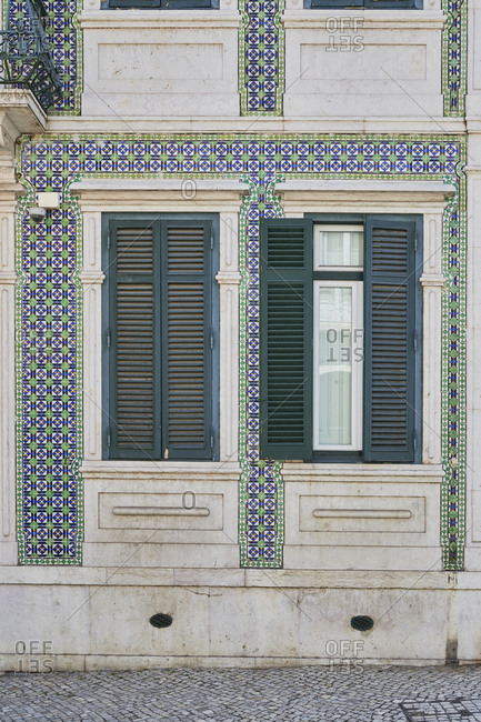 Home exterior with decorated tile around window with shutters, Lapa neighborhood, Lisbon, Portugal
