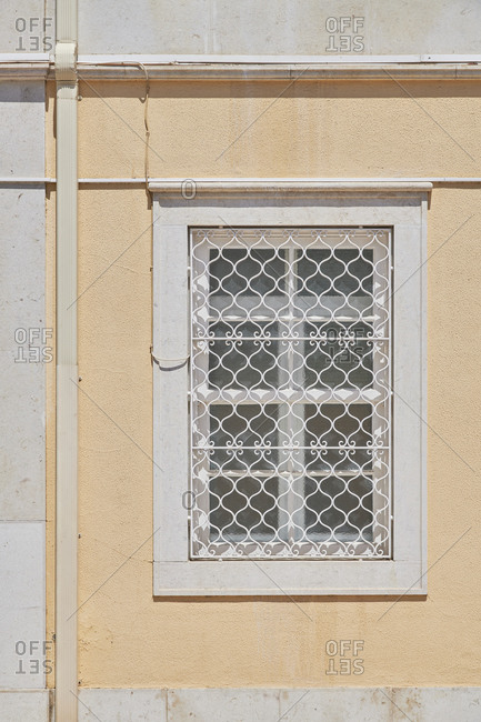 Window on yellow home with decorative security bars, Lapa neighborhood, Lisbon, Portugal