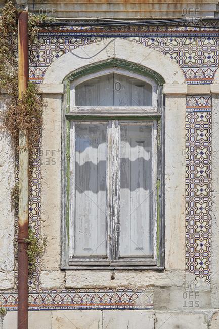Home exterior with Moorish tile around window, Lapa neighborhood, Lisbon, Portugal
