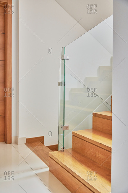Internal wooden staircase with a glass railing