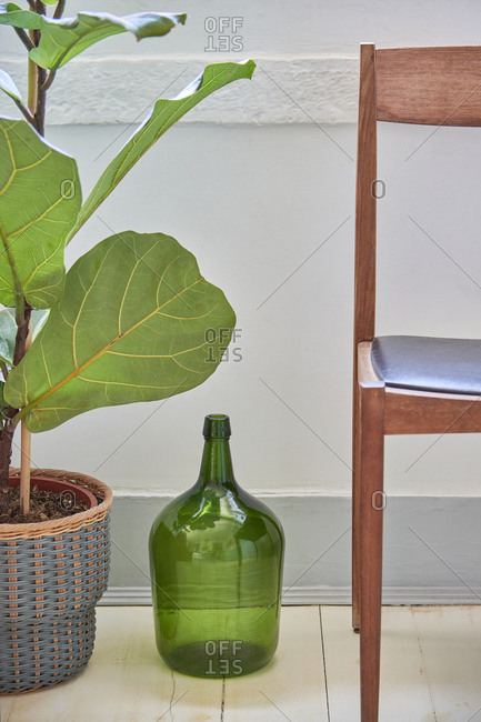 Green decorative jug beside plant and chair, Lisbon, Portugal