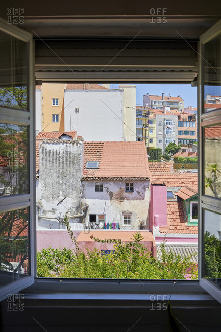 View of multicolored apartments through open window in the Lapa neighborhood in Lisbon, Portugal