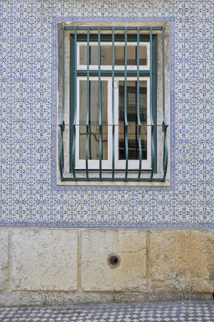 Blue tile around window with security bars on home in the Lapa neighborhood, Lisbon, Portugal