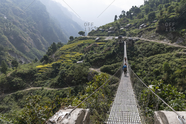 Suspension bridge, Nepal with trekker
