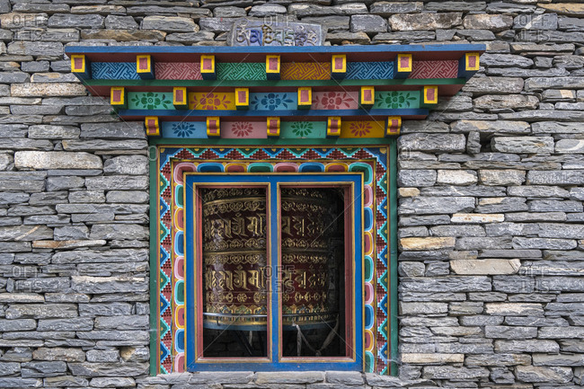 October 28, 2019: View of a prayer wheel through a window of the Namla monastery near Namrung in Nepal