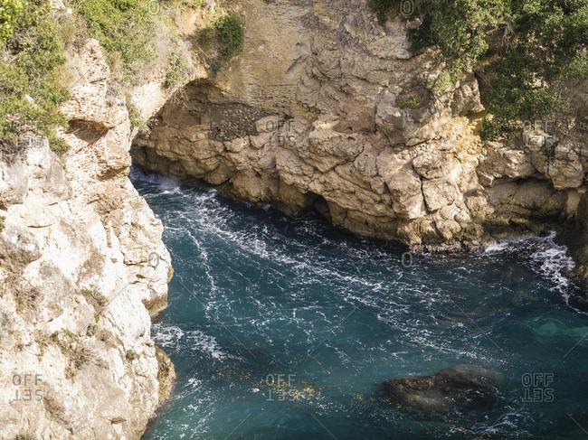 Blue waves crashing on coast of Sorrento, Italy