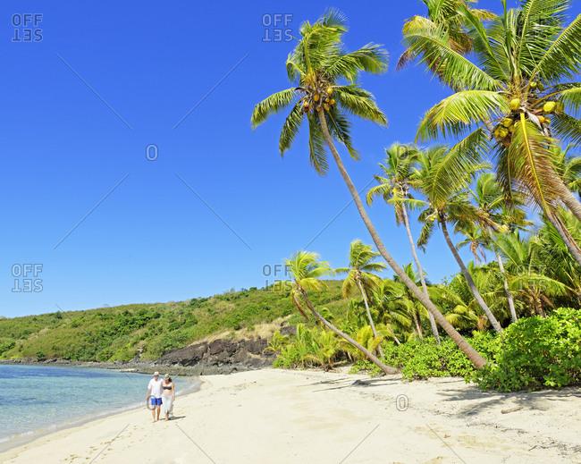 Couple walking on a tropical beach, Drawaqa Island, Yasawa island group, Fiji, South Pacific islands