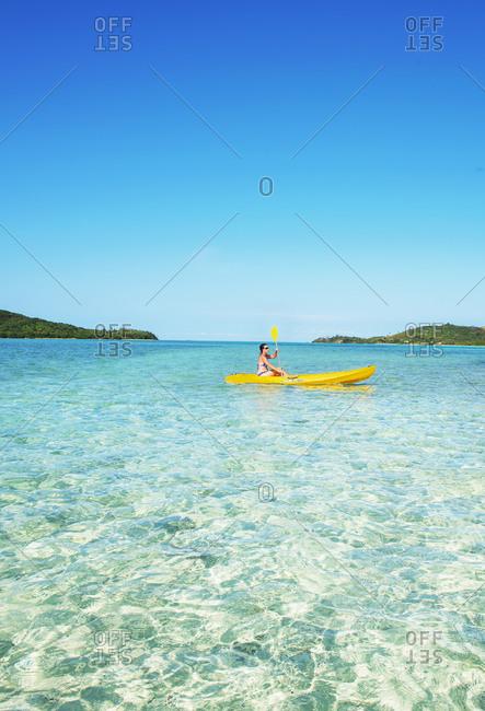 July 25, 2019: Woman sea kayaking, Waya island, Yasawa island group, Fiji