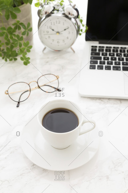 White cup of black coffee on saucer, open laptop, glasses and beautiful classic alarm clock with white face next to potted plant on top of table with marble surface, from high angle