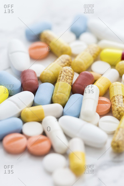 Pile of colorful medicine pills, white, blue, yellow and red, sitting on white background and viewed from high angle in close-up with tilt-shift selective focus