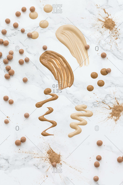 Samples of light beige skin tone cosmetics, arranged on marble surface with smears of liquid concealer, piles of powder and powder balls, isolated in full frame, viewed from above
