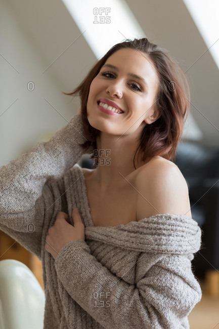 Beautiful young brunette woman with bare shoulder, wearing grey sweater, posing at camera and smiling, with her head to her hair.