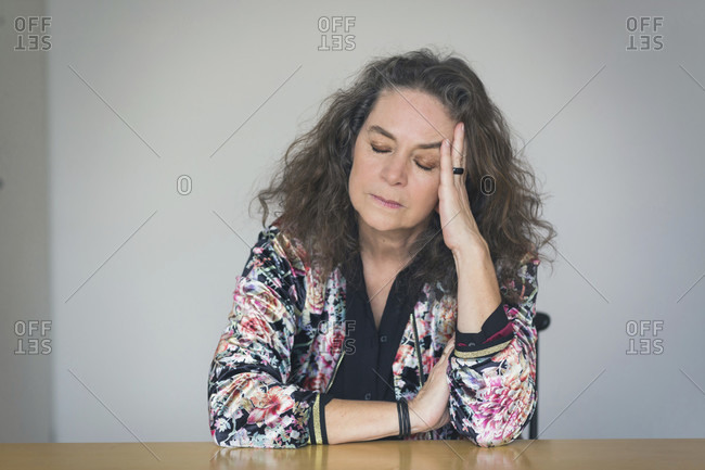 Depressed or unwell pretty middle-aged woman seated at a table indoors resting her head on her hand with closed eyes and a serious withdrawn expression