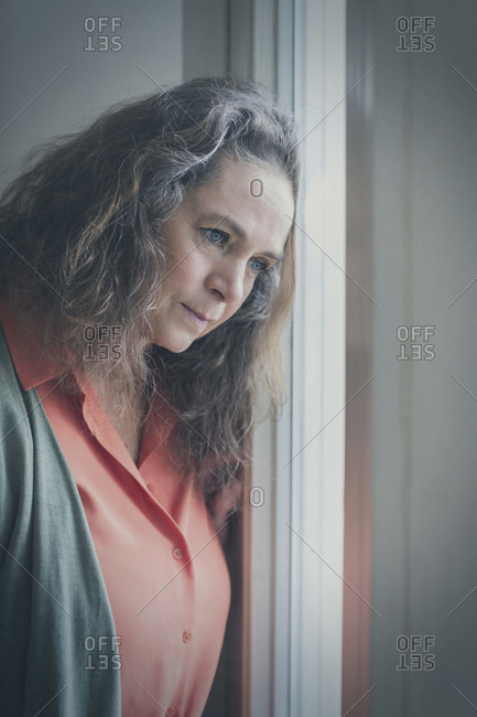 Thoughtful woman leaning her head on a window staring outside watching something intently