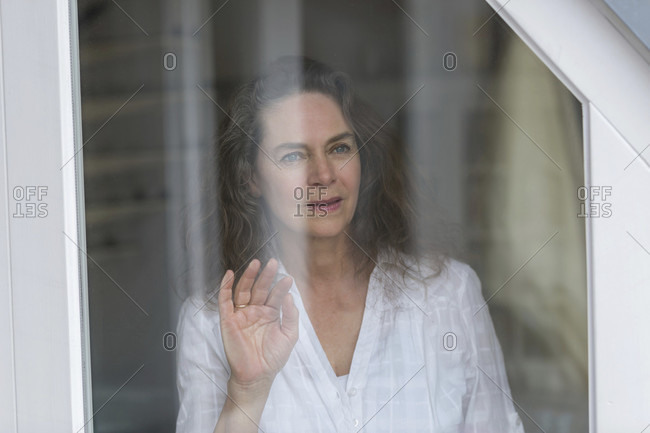 Middle aged woman looking out of the window emoitons