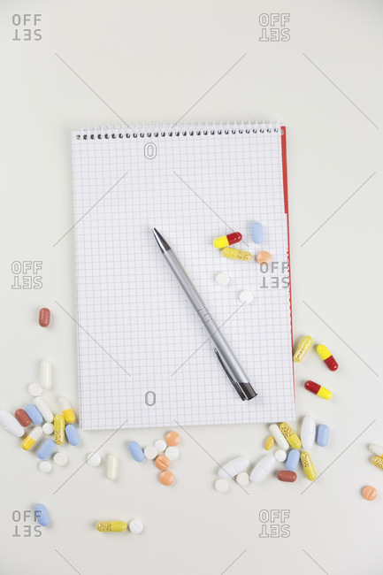 Various colorful pills next to notepad closeup view from above