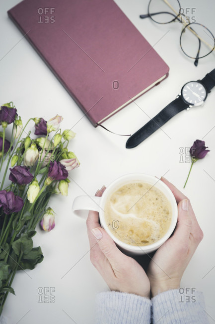 Woman clasping a cup of coffee in her hands surrounded by a bunch of fresh flowers, wristwatch, closed, diary, notebook or journal and eyeglasses viewed from above