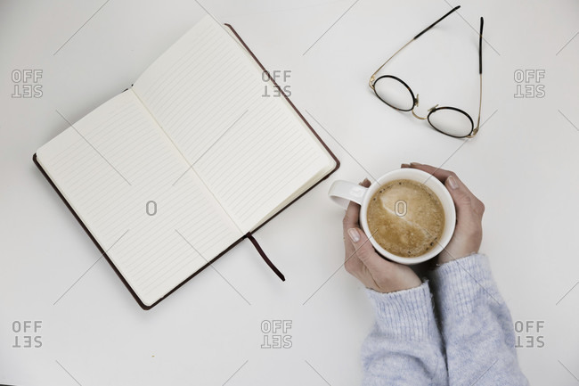 Woman clasping a cup of hot coffee with an open blank notebook and her reading glasses