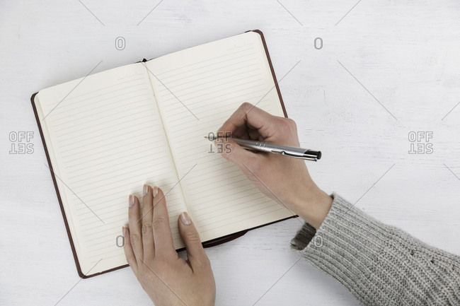 Woman writing in a blank open diary, notebook or journal with a ballpoint pen in a communications and business concept