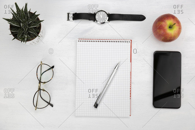 Business, study or time management concept with a blank notepad and pen surrounded by a mobile phone, red apple, wristwatch, potted plant and spectacles viewed from above