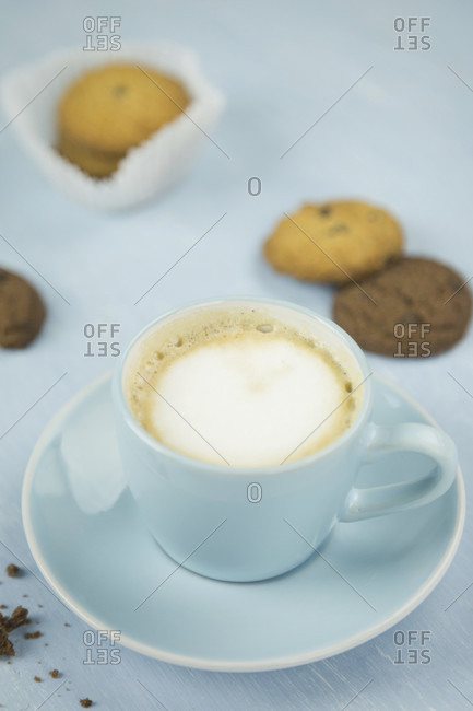 Cup of coffee among cookies against plain blue background