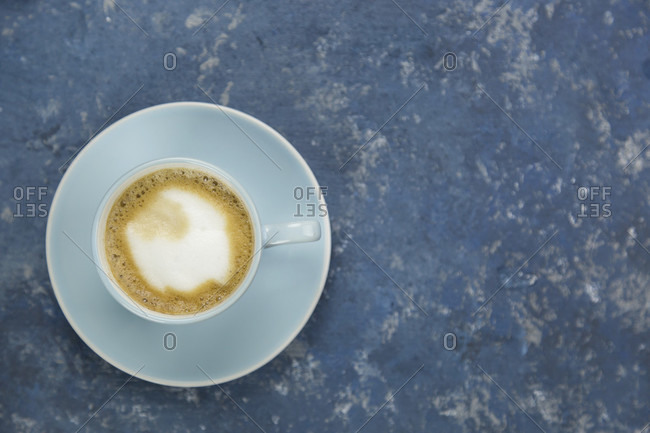 Cup of cappuccino against blue background with copy space