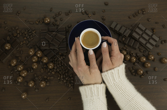 Woman wearing a woolly jersey drinking fresh espresso coffee in an overhead view of her hand and the cup surrounded by assorted dark and milk chocolate