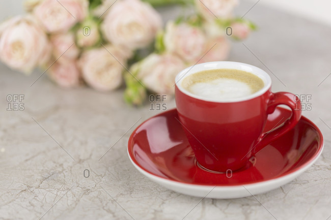 Cup of fresh frothy coffee on a marble table with a bunch of pink roses to the side in a conceptual image of love or relaxation, top down view