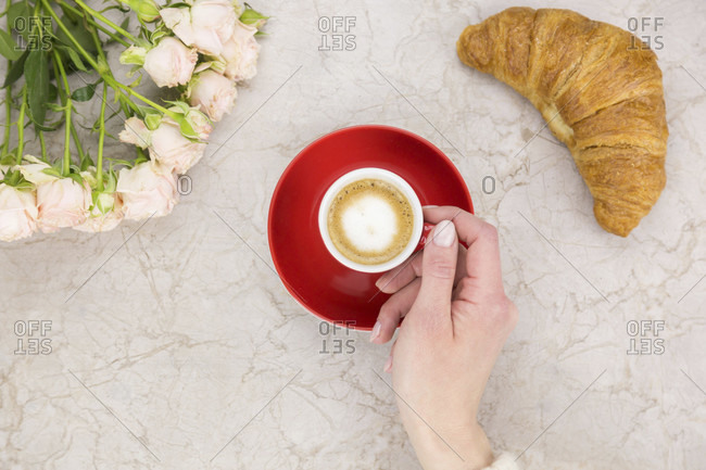 Hand of a woman enjoying coffee in a colorful red cup and saucer and a fresh croissant with a bunch of pink roses to the side on a marble surface