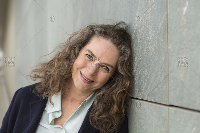 Natural attractive woman with long curly hair with a sweet genuine smile leaning against a grey stone wall looking at the camera in a close up portrait
