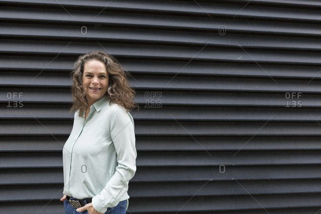 Attractive woman with a vivacious smile and long curly brown hair posing in front of a black ridged urban wall with copy space