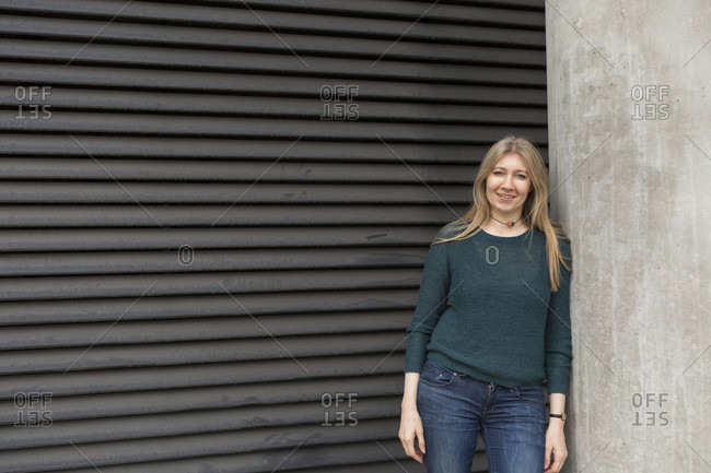 Portrait of attractive mature woman in casuals leaning on wall in city