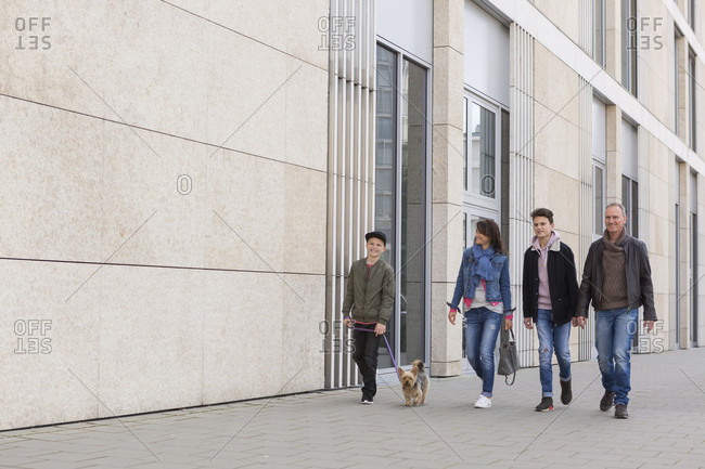 Family with teenage boys and a small dog on a lead walking in town alongside a commercial building along the sidewalk with copy space on the wall