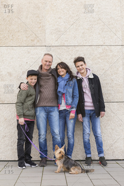 Happy affectionate family with two young boys and their dog posing arm in arm in front of a commercial building smiling at the camera
