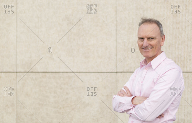 Portrait of confident mature businessman wearing pink shirt while standing arms crossed by wall in city