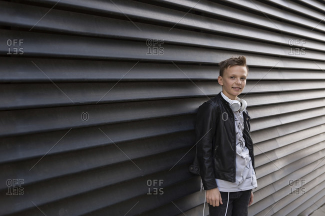 Portrait of fashionable boy wearing black leather jacket while leaning on patterned wall in city